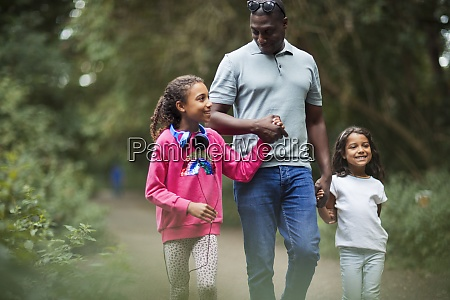 happy father and daughters holding hands