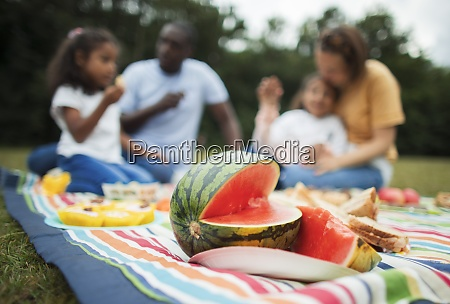family enjoying fresh watermelon on picnic
