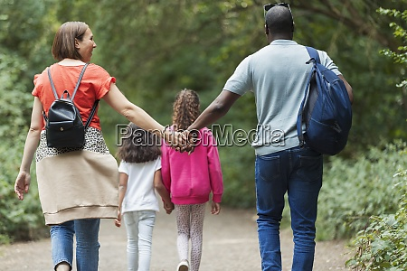 affectionate family holding hands hiking on