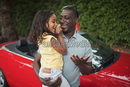 happy father holding daughter by convertible