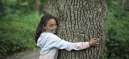 serene girl hugging tree trunk in