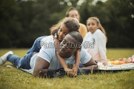affectionate daughter hugging father on picnic