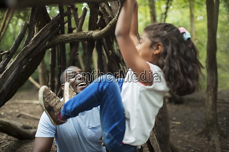 father watching daughter hang from branch