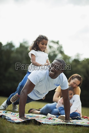 playful father doing push ups with