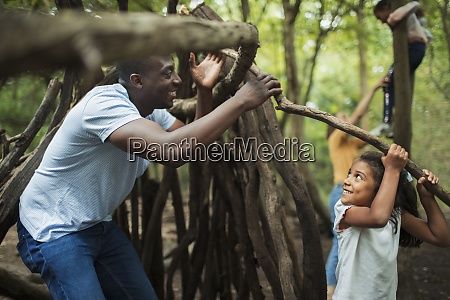 father and daughter building teepee with