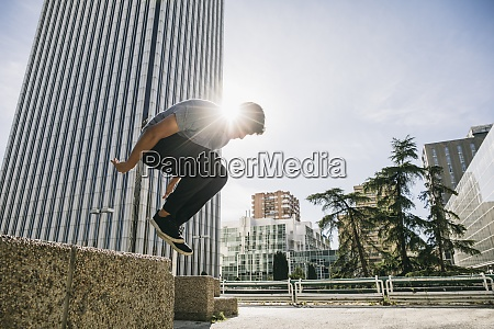 young man performing parkour over retaining