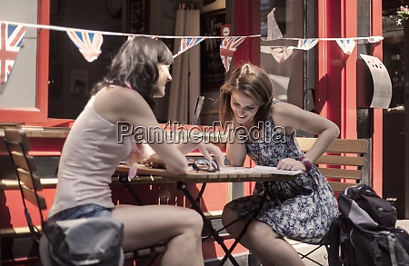 cheerful female friends sitting at table