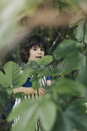 cute boy standing while hiding behind