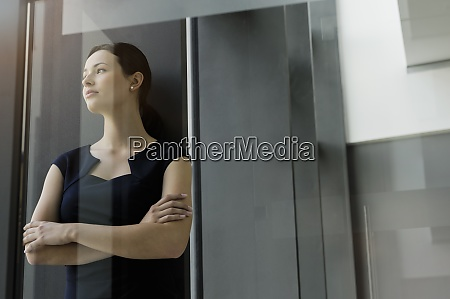 thoughtful businesswoman with arms crossed standing