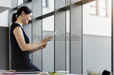 smiling businesswoman using digital tablet while
