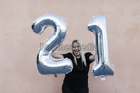 cheerful young woman holding number 21