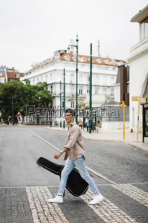 smiling man carrying guitar while crossing