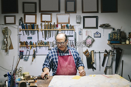 man working while standing by workbench
