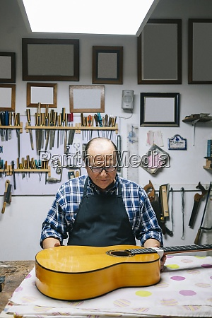 luthier repairing guitar while standing at