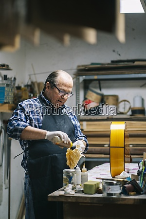 luthier polishing guitar while standing by