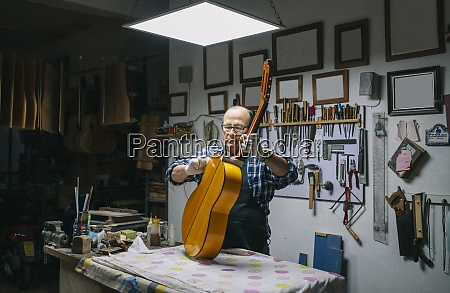 man holding guitar on workbench while