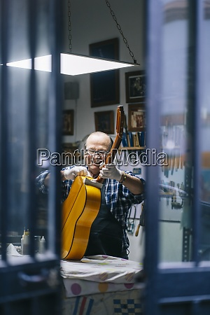 smiling man cleaning guitar while working