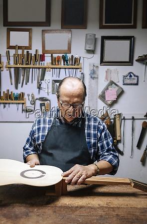 man making guitar while standing at