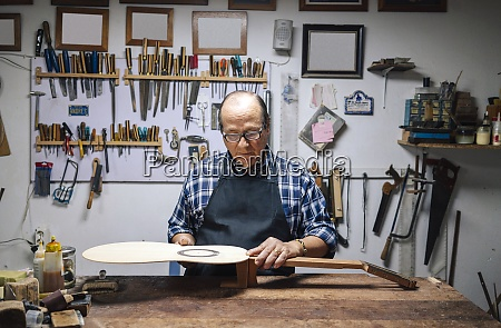 senior luthier manufacturing guitar while standing