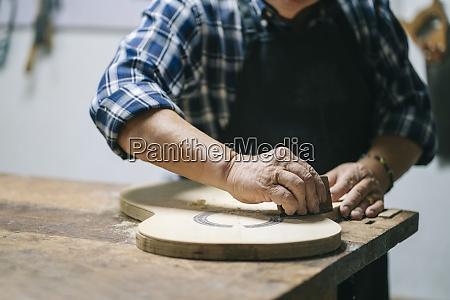 man molding shape of guitar while