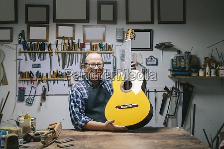 smiling man holding guitar while standing
