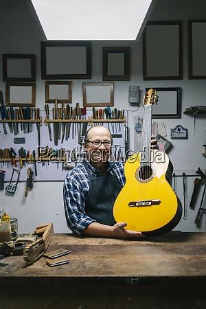 smiling craftsman holding guitar while standing