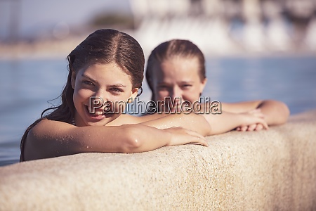 smiling friends in swimming pool on