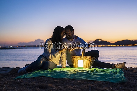 romantic couple with drinks sitting at