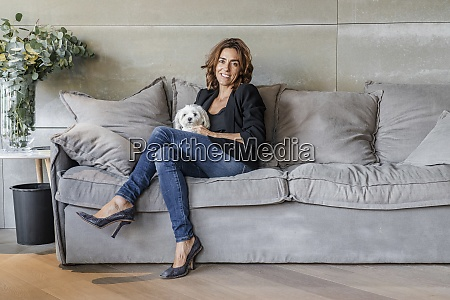smiling woman sitting with dog on