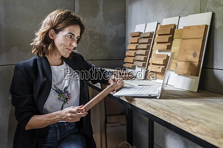 smiling woman holding wood tile while