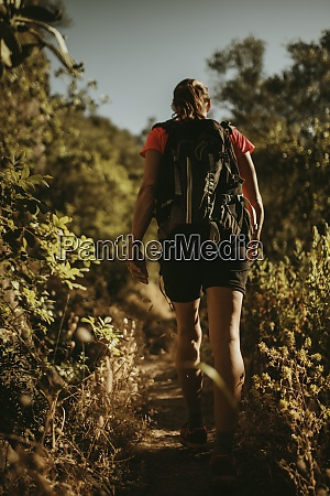 woman with backpack trekking on path