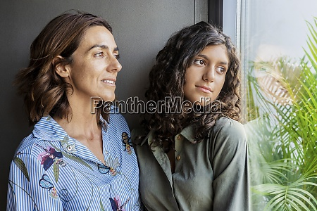 mother and daughter looking through window