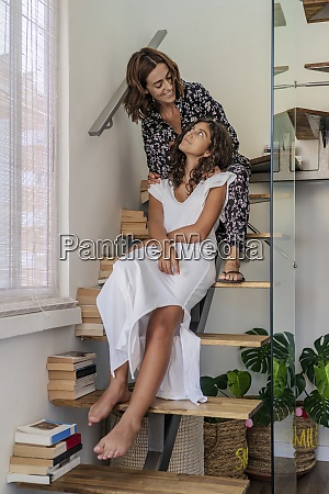 mother and daughter sitting on staircase