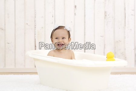 portrait of laughing baby girl bathing
