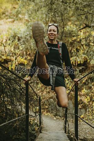 smiling woman swinging on bridge railing