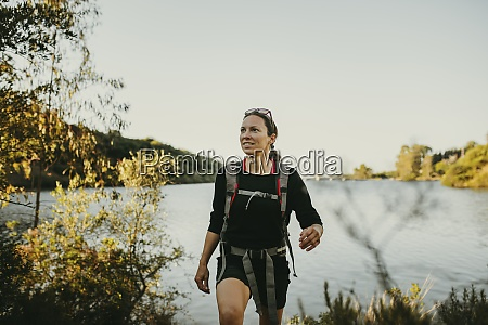 woman walking against river by sierra