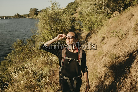 smiling woman trekking on footpath at