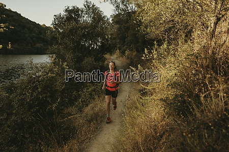 smiling woman running on footpath at