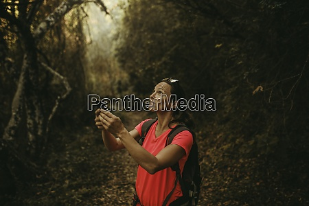 woman holding mobile phone while standing