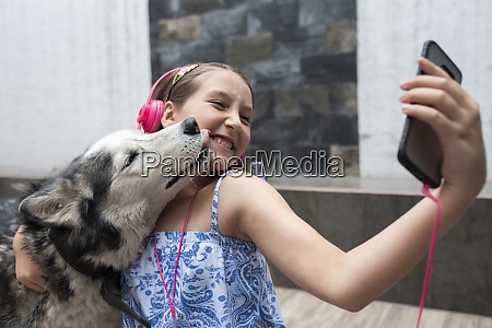 girl taking selfie with dog through