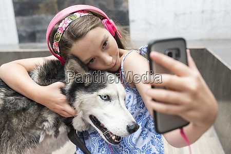 girl with headphone taking selfie with