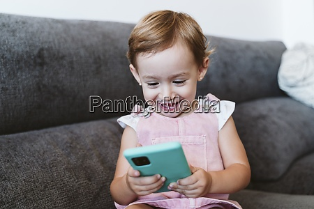 smiling baby girl using mobile phone