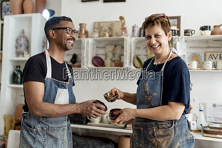 smiling artists holding ceramics while standing