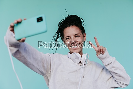 smiling woman making peace sign while