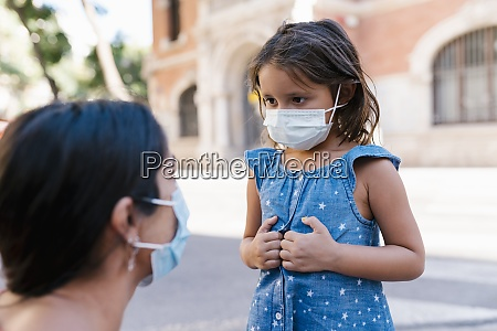 girl wearing mask looking at mother