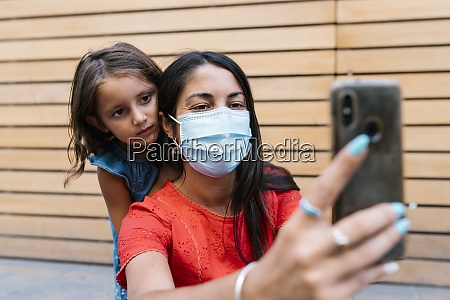 mother wearing mask taking selfie with