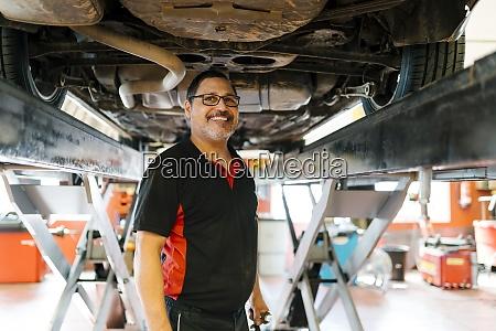 smiling male mechanic standing below car