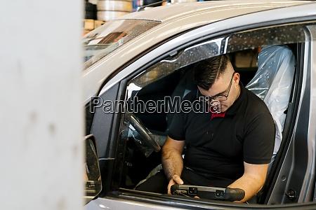 mechanic examining car while sitting on