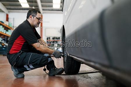 auto mechanic adjusting car tire in