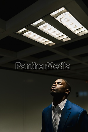 african businessman with eyes closed standing